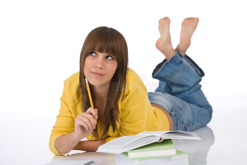 Estudante - o adolescente fêmea escreve trabalhos de casa pensa fotografia de stock