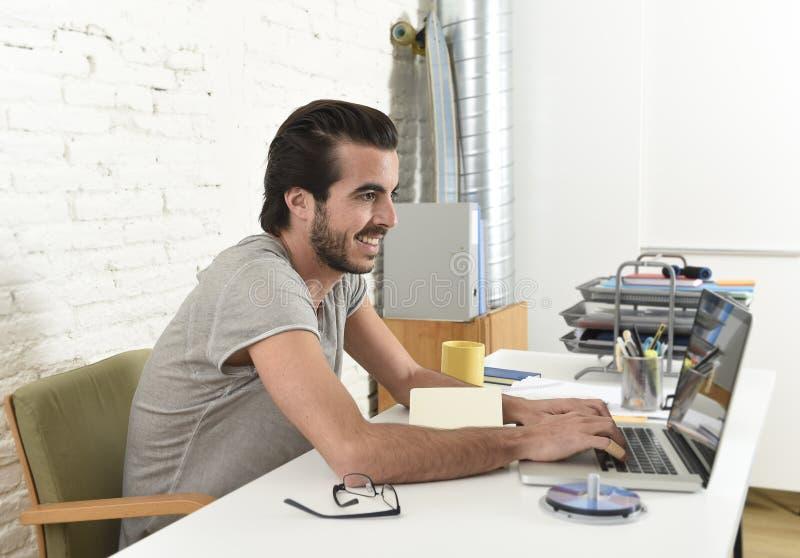 Estudante ou homem de negócios moderno novo do estilo do moderno que trabalham com o escritório do portátil em casa foto de stock royalty free