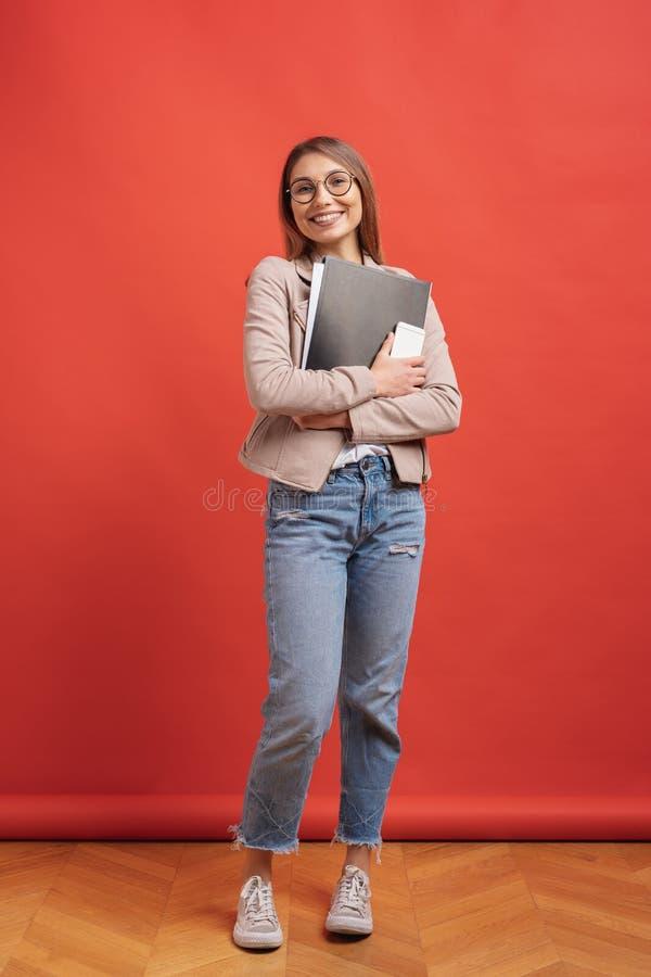 Estudante ou interno de sorriso novo nos mon?culos que est?o com um dobrador no fundo vermelho foto de stock