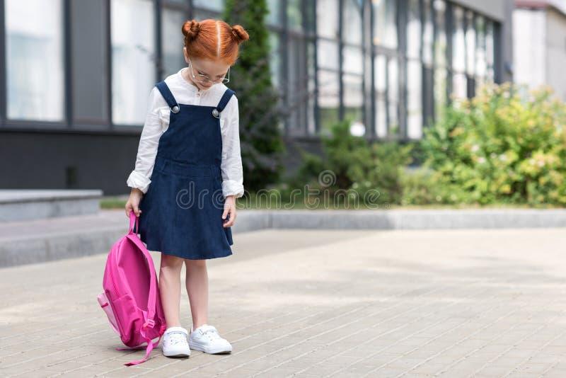 estudante pequena adorável que guarda a trouxa e que olha para baixo imagem de stock royalty free