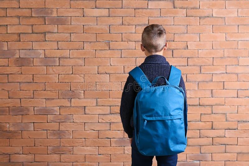 Estudante pequena bonito com a trouxa contra a parede de tijolo foto de stock royalty free