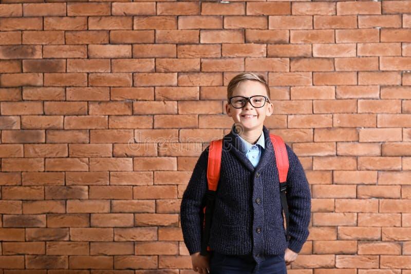 Estudante pequena bonito com a trouxa contra a parede de tijolo foto de stock