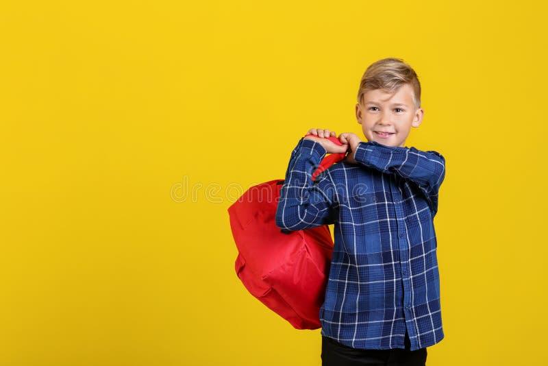 Estudante pequena bonito com a trouxa no fundo da cor foto de stock