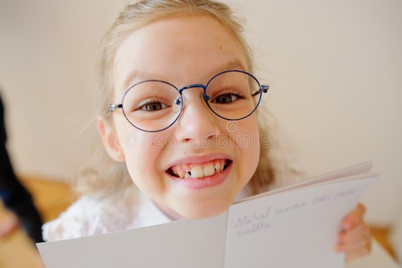 A estudante pequena bonito nos vidros mostra seu caderno fotografia de stock royalty free