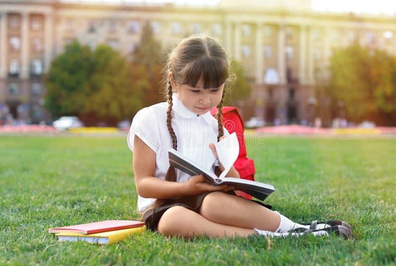Estudante pequena bonito que senta-se na grama verde e no livro de leitura fotografia de stock