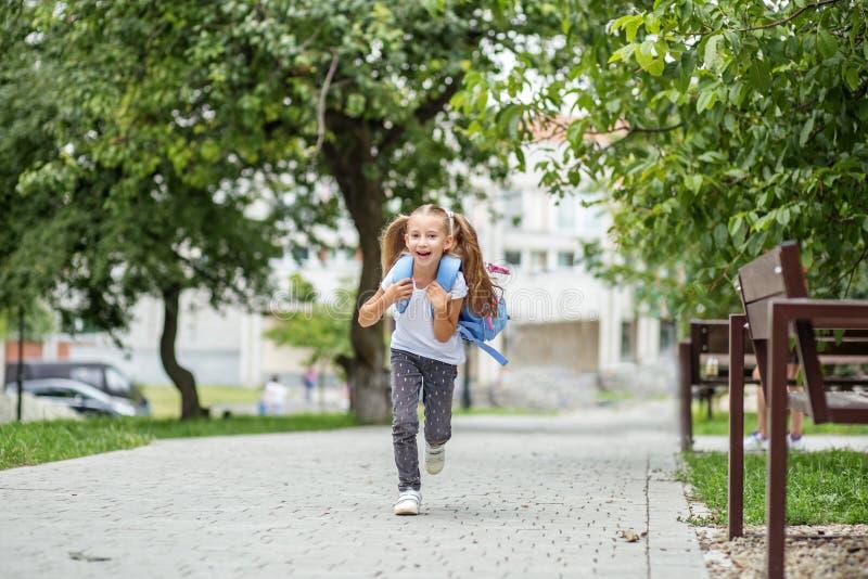 A estudante pequena está correndo com uma trouxa e um riso O conceito da escola, estudo, educação, amizade, infância imagens de stock
