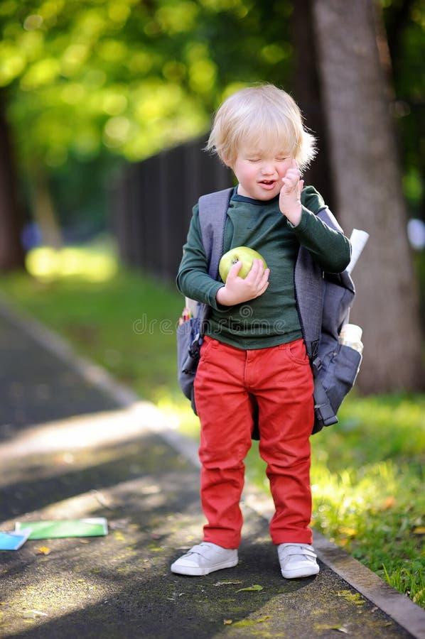 Estudante pequena infeliz no dia ensolarado do outono De volta ao conceito da escola foto de stock