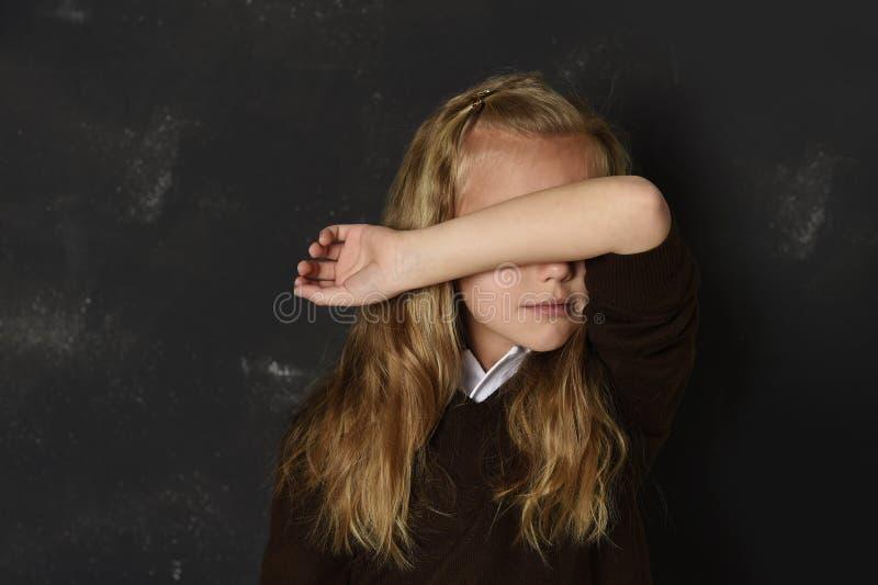 Estudante pequena na coberta uniforme sua cara com sua vítima triste de grito do braço de tiranizar na escola foto de stock royalty free
