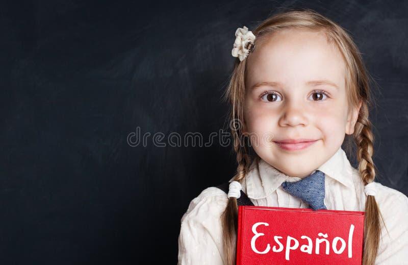 Estudante pequeno da criança que aprende o espanhol no quadro da sala de aula foto de stock royalty free