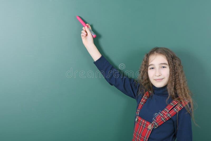 Estudante perto da administração da escola verde A menina brincalhão nova guarda uma pena vermelha em sua mão fotografia de stock