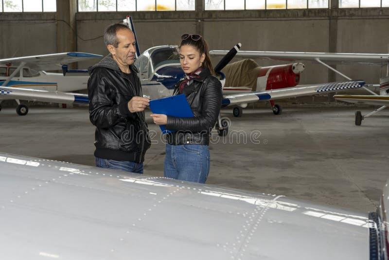 Estudante Pilot e instrutor Check do voo um avião para a segurança em um hangar imagens de stock royalty free