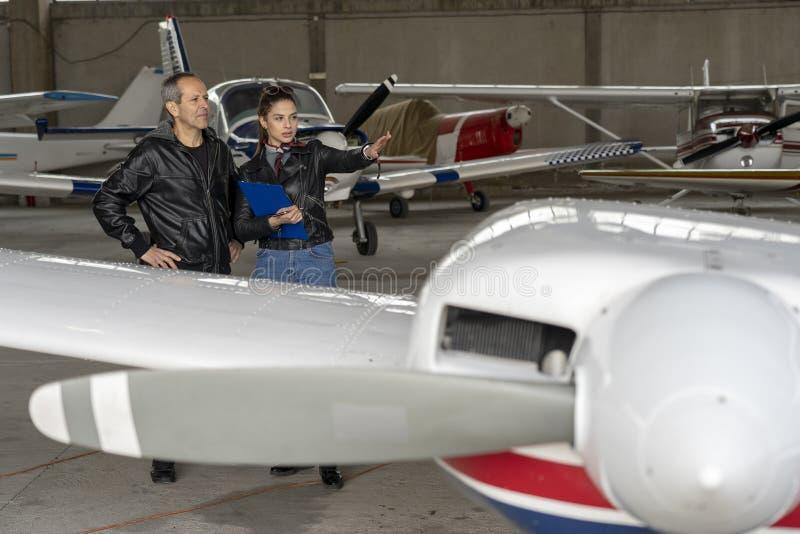 Estudante Pilot e instrutor Check um avião para a segurança em um hangar imagens de stock
