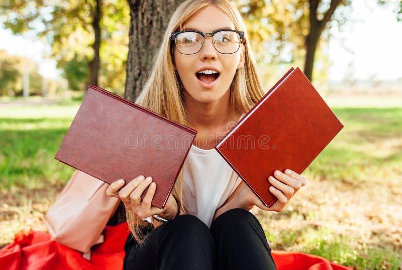 Estudante positivo com vidros, levantamento engraçado com os livros que guardam t imagem de stock