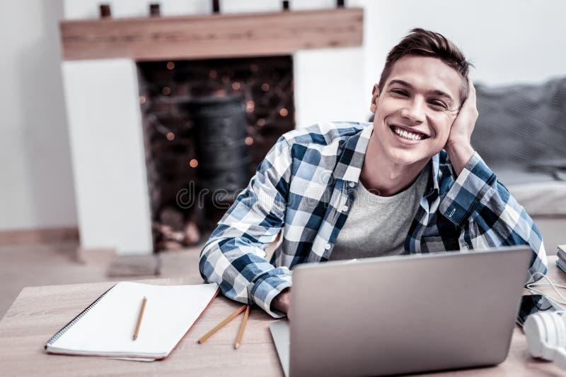 Estudante positivo que inclina sua cabeça em sua mão e que sorri ao usar seu portátil imagens de stock royalty free