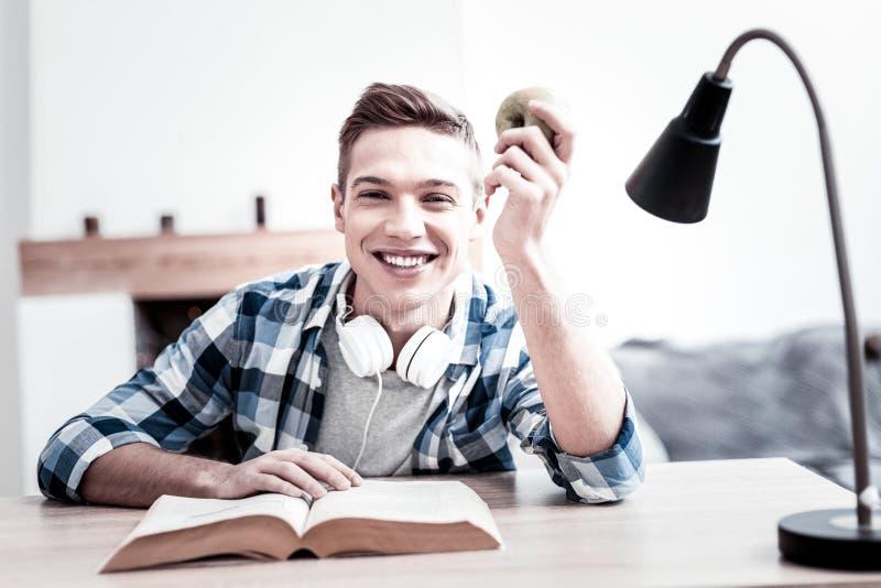 Estudante positivo que sorri ao ler e ao guardar a maçã imagens de stock royalty free