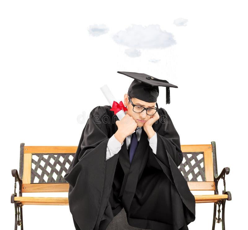 Estudante preocupado no banco que guarda o diploma e uma nuvem que flutua o ov fotos de stock