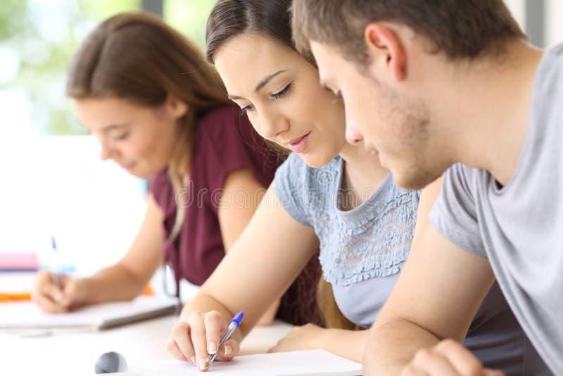 Estudante que ajuda a um colega na sala de aula fotografia de stock royalty free