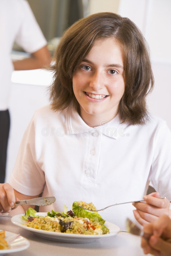 Estudante que aprecia seu almoço na escola imagens de stock royalty free