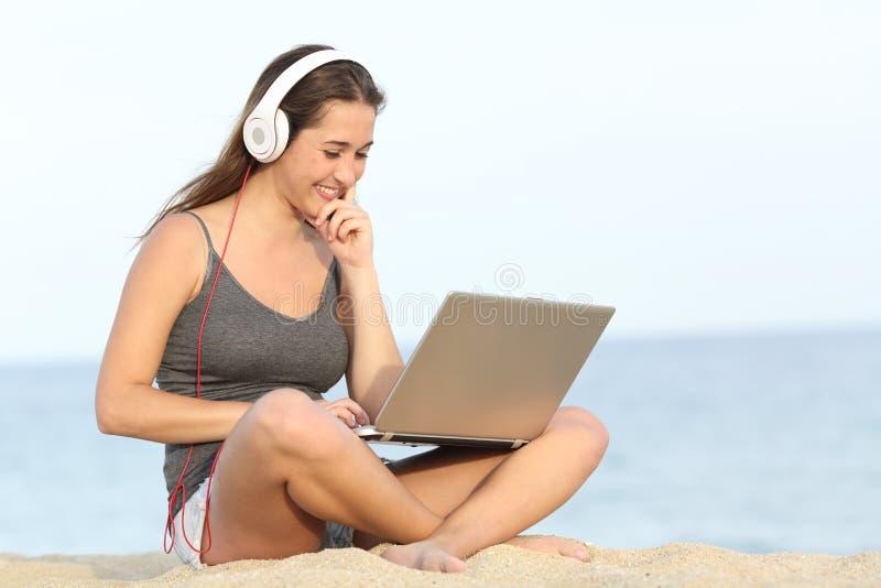 Estudante que aprende o curso com um portátil na praia imagem de stock