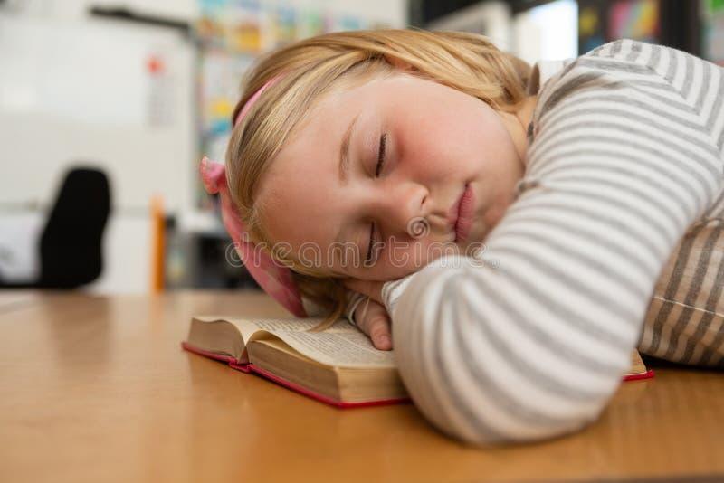 Estudante que dorme no livro na mesa na sala de aula foto de stock