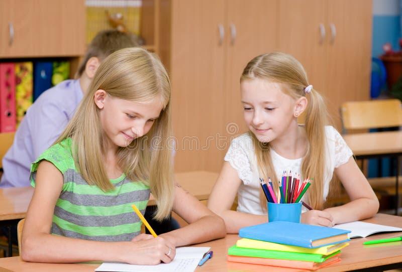 Estudante que engana-se no exame, olhando a escrita de um amigo fotos de stock