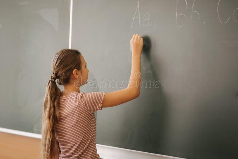 Estudante que escreve algo no quadro-negro na sala de aula fotos de stock