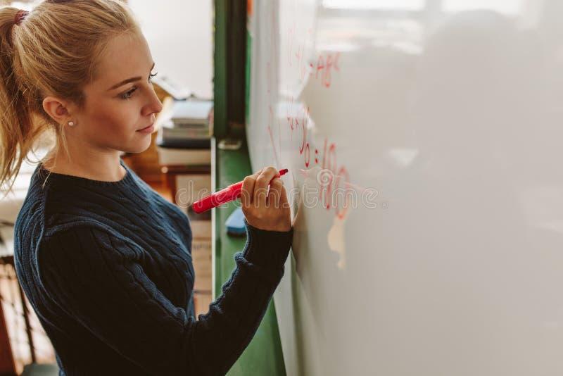 Estudante que escreve a bordo durante a classe das matemáticas fotografia de stock royalty free