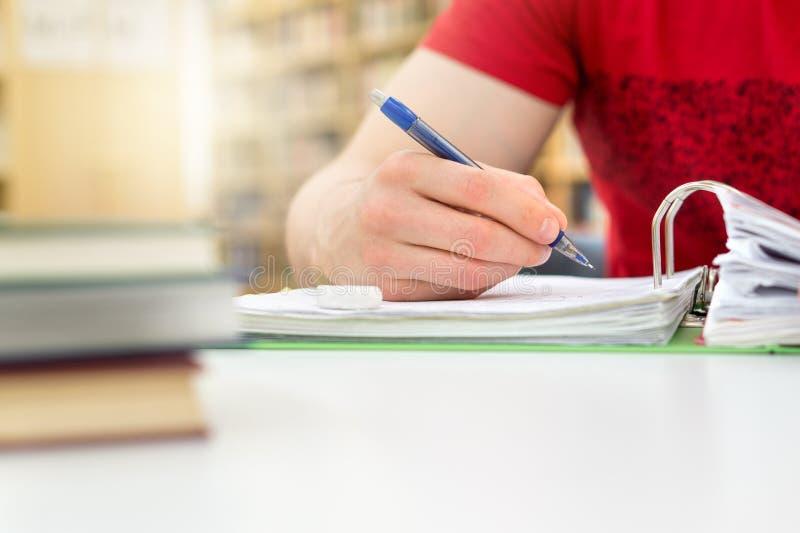 Estudante que estuda e que escreve notas em público ou biblioteca escolar foto de stock royalty free