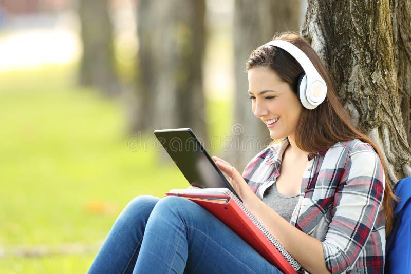 Estudante que estuda a escuta na linha lições imagens de stock royalty free