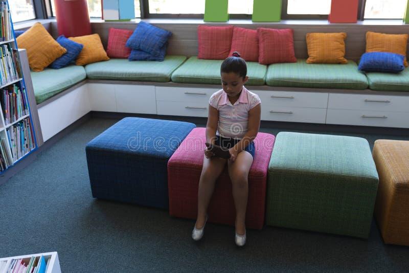 Estudante que estuda na tabuleta digital ao sentar-se no sofá na biblioteca escolar imagem de stock royalty free
