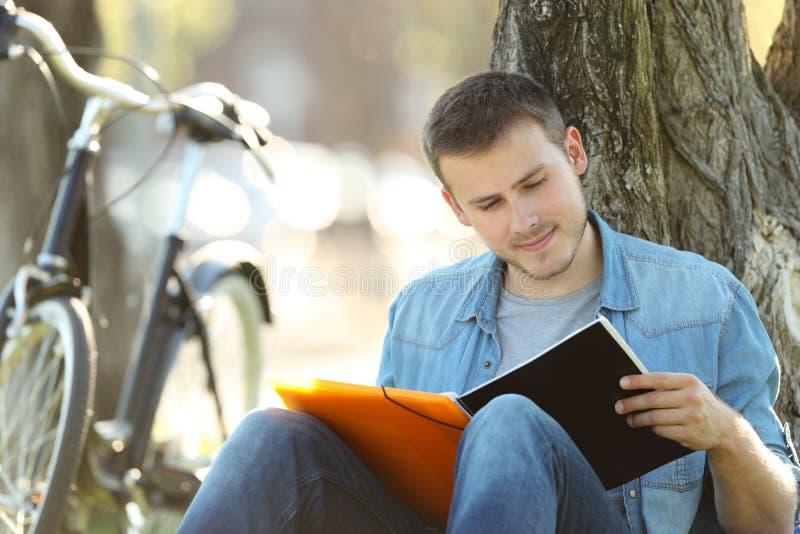 Estudante que estuda notas da leitura fora foto de stock