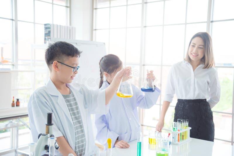 Estudante que faz a experiência com seu professor na sala de aula da química imagens de stock