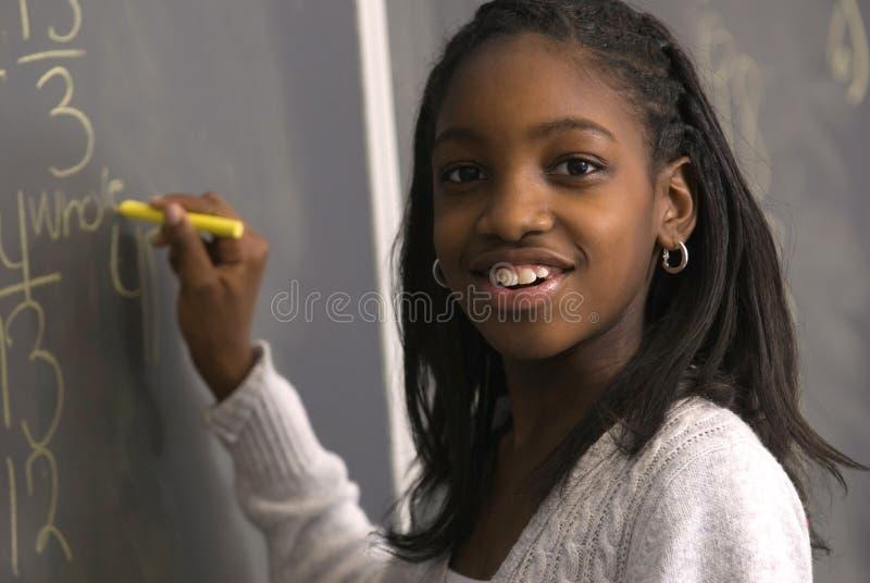 Estudante que faz a matemática na placa de giz imagens de stock