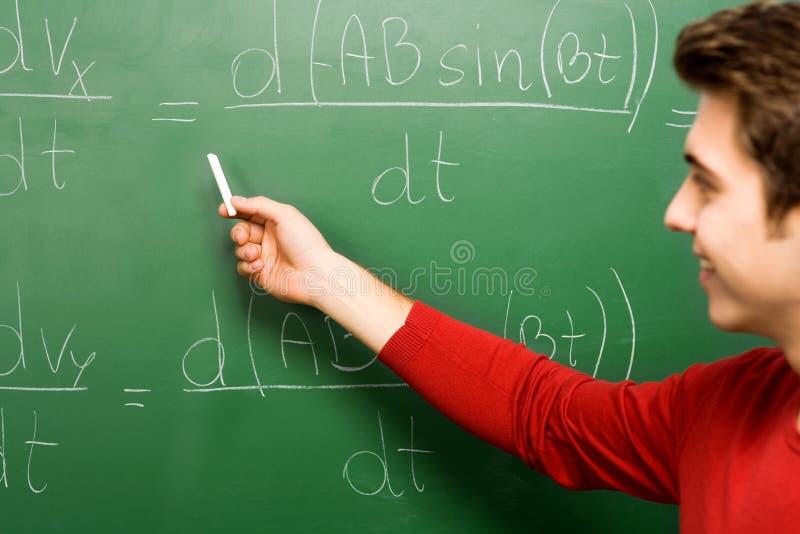 Estudante que faz a matemática no quadro fotografia de stock