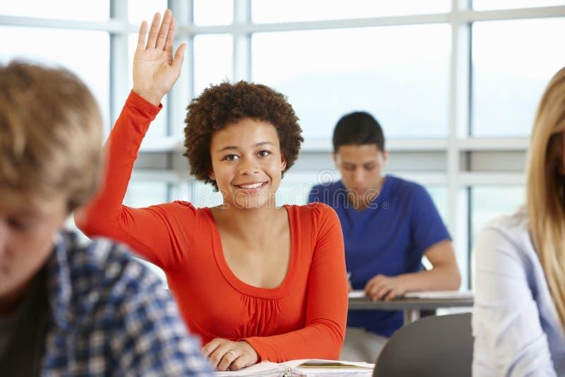 Estudante que faz a pergunta na classe imagem de stock