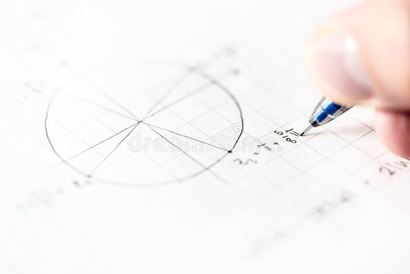 Estudante que faz trabalhos de casa da matemática ou teste da matemática na turma escolar imagem de stock