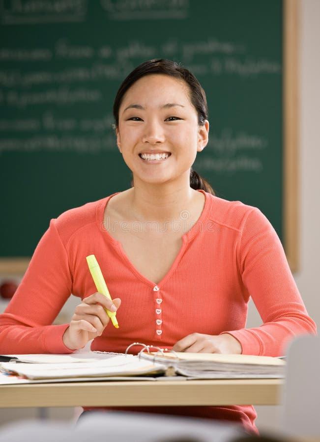 Estudante que faz trabalhos de casa na sala de aula da escola imagens de stock royalty free