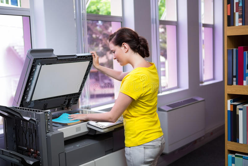 Estudante que fotocopia seu livro na biblioteca imagem de stock