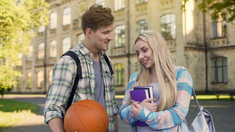Estudante que guarda a bola, flertando com a menina bonita perto da universidade, pedindo a data fotos de stock