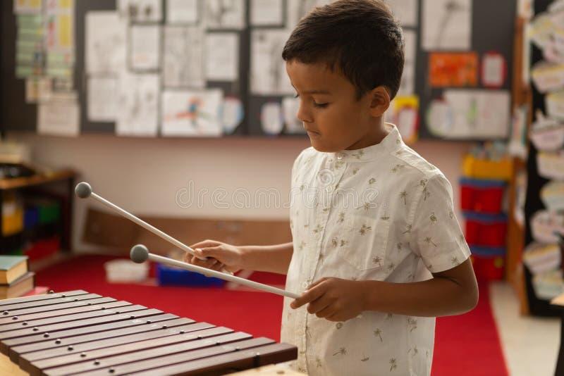 Estudante que joga o xilofone em uma sala de aula imagens de stock