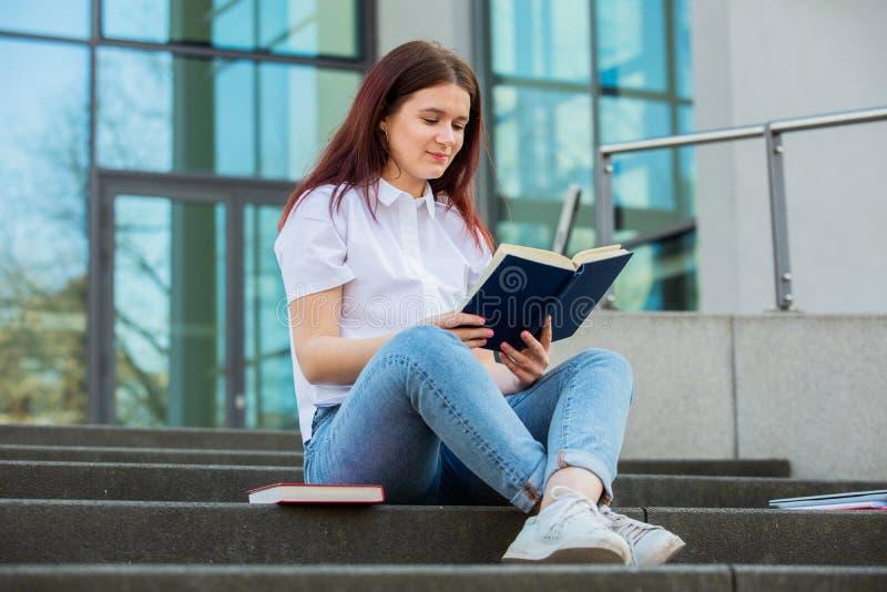 Estudante que lê seu livro favorito imagem de stock royalty free