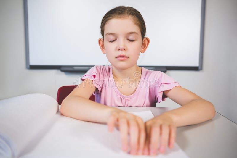 Estudante que lê um livro do braile na sala de aula imagem de stock