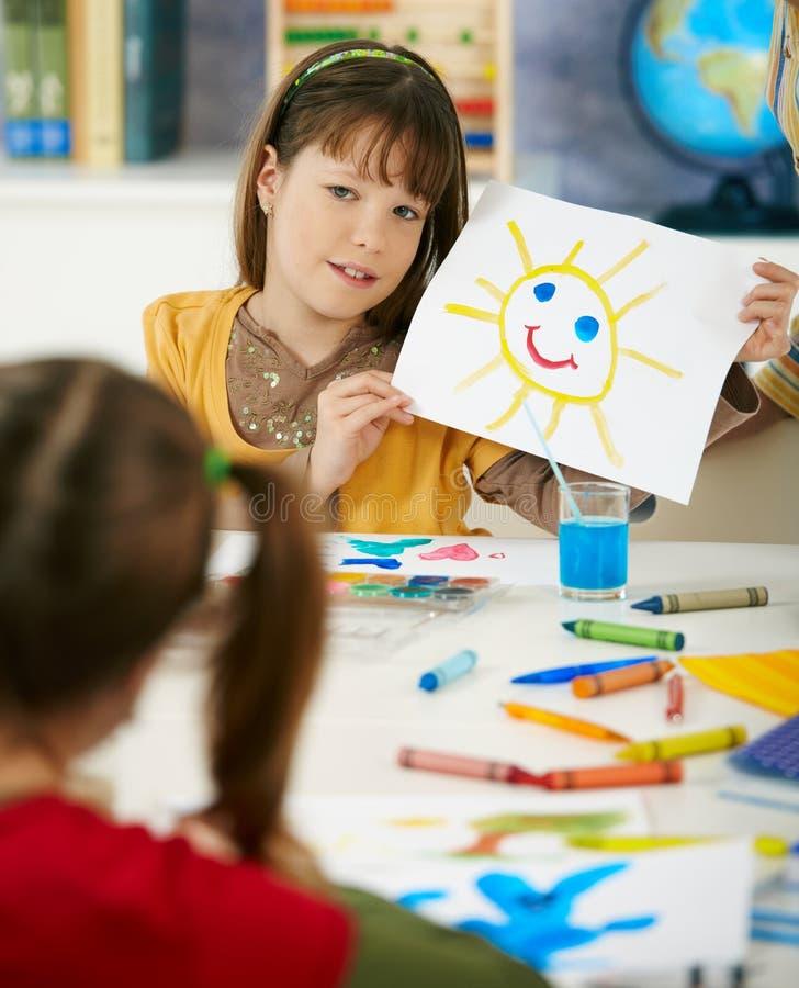 Estudante que mostra a pintura na classe de arte imagem de stock