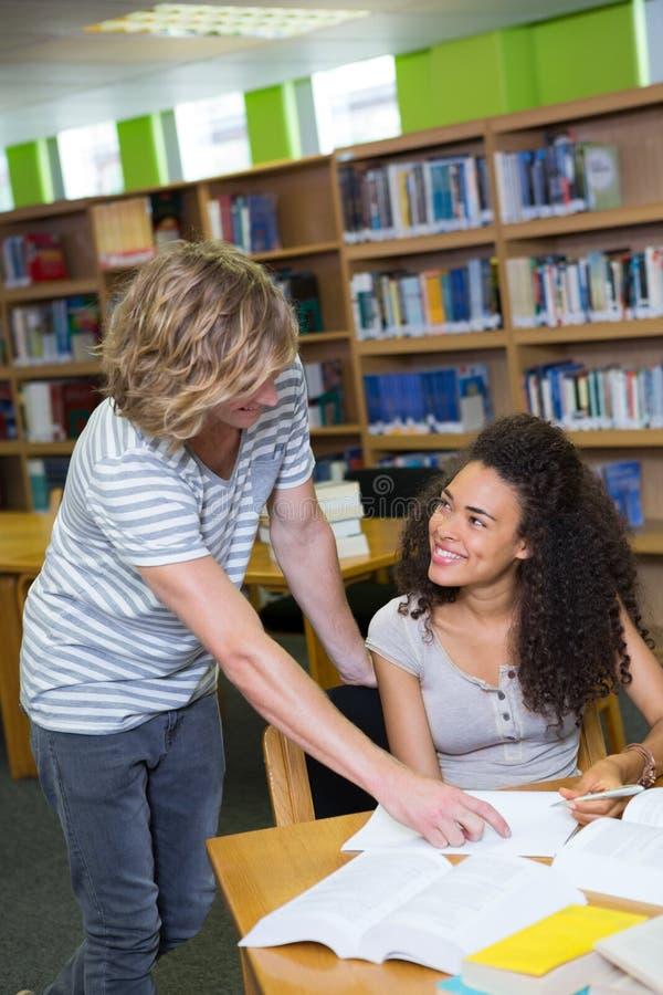 Estudante que obtém a ajuda do colega na biblioteca imagem de stock royalty free