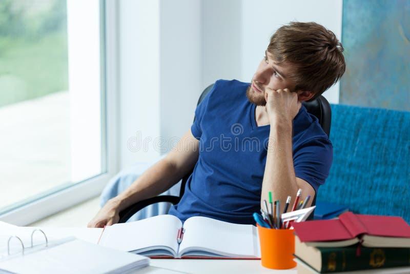 Estudante que olha através da janela imagem de stock