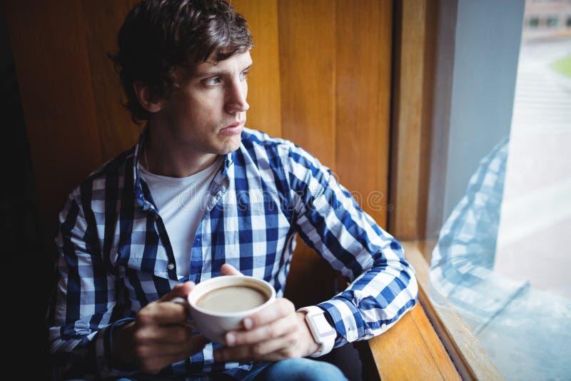 Estudante que olha através da janela ao comer o café fotos de stock royalty free