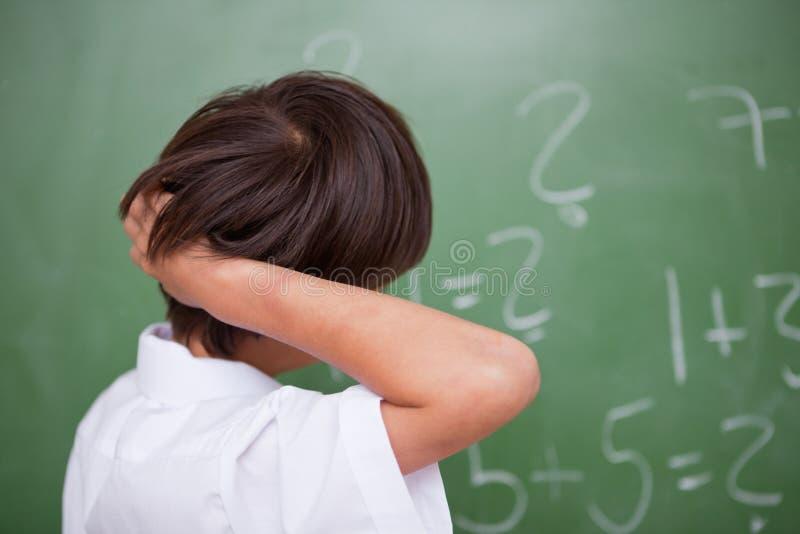 Estudante que pensa ao riscar a parte traseira de sua cabeça fotografia de stock