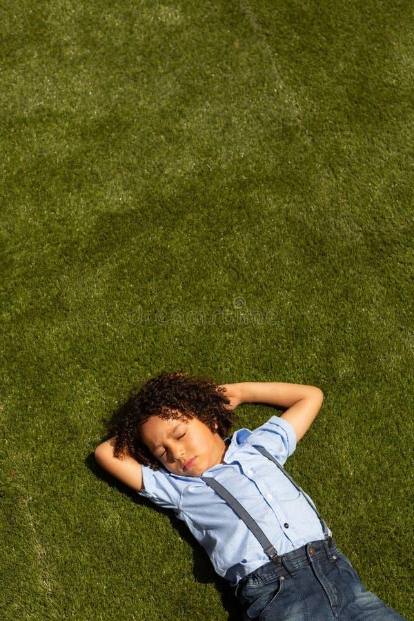 Estudante que relaxa no campo de jogos da escola foto de stock royalty free