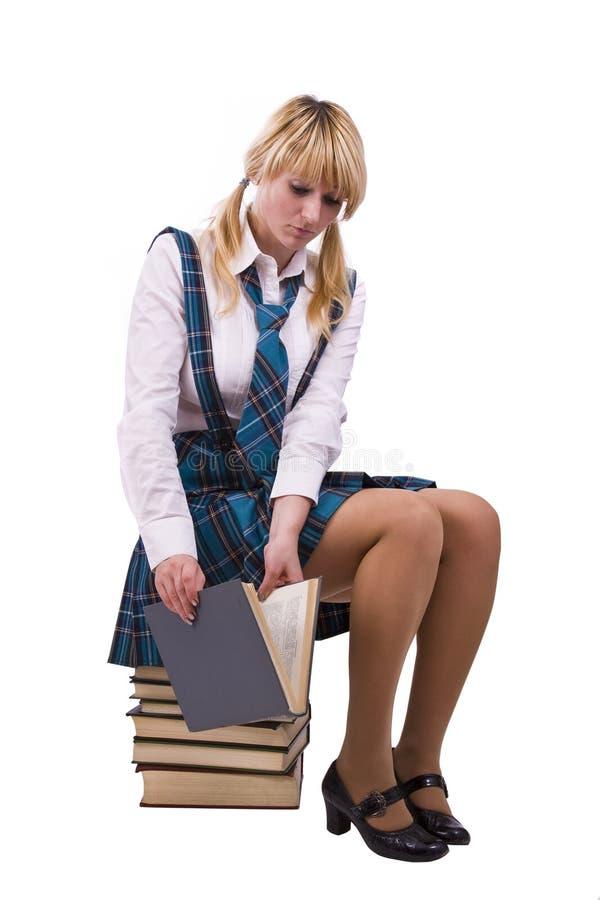Estudante que senta-se em livros e em relógio furtiva imagens de stock