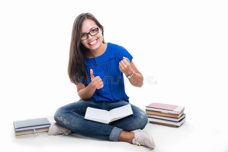 Estudante que senta-se fazendo o gesto do vencedor com livros ao redor imagem de stock